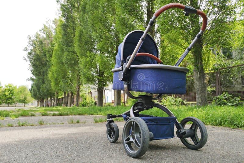 Um bebê do pram no parque em um dia ensolarado Pai que anda com o transporte no parque da cidade imagens de stock royalty free
