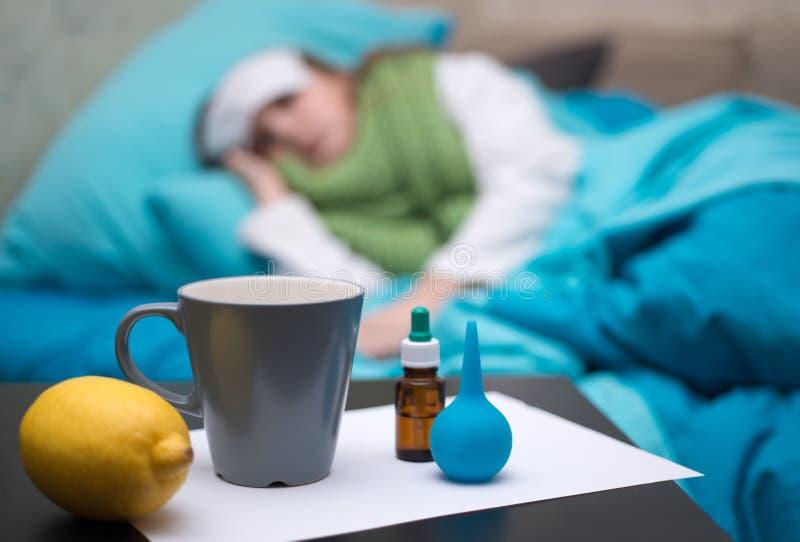 Um bebê doente que encontra-se na cama na frente de sua cara droga-se fotografia de stock