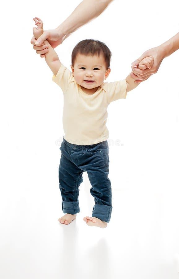 Um bebê está aprendendo o passeio isolado no branco, os olhares da menina da criança na câmera e o sorriso imagens de stock
