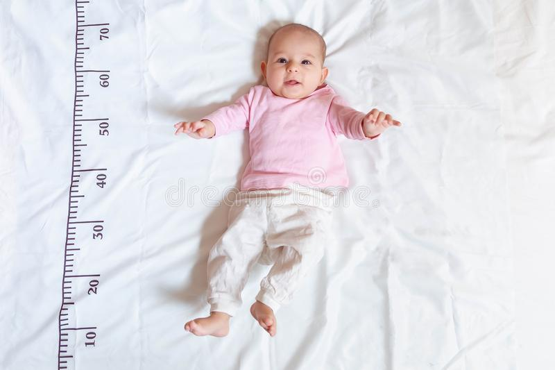 Um bebê feliz de quatro meses na roupa branca cor-de-rosa que encontra-se em uma cama em que uma régua de medição para o crescime imagens de stock