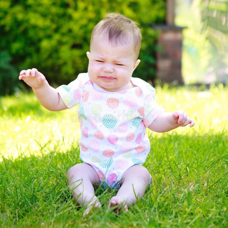 Um bebê gritando e contorcendo em uma veste que senta-se na grama imagens de stock royalty free