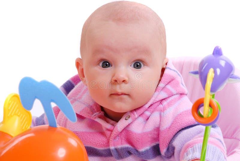 Um bebê joga com brinquedos fotos de stock royalty free