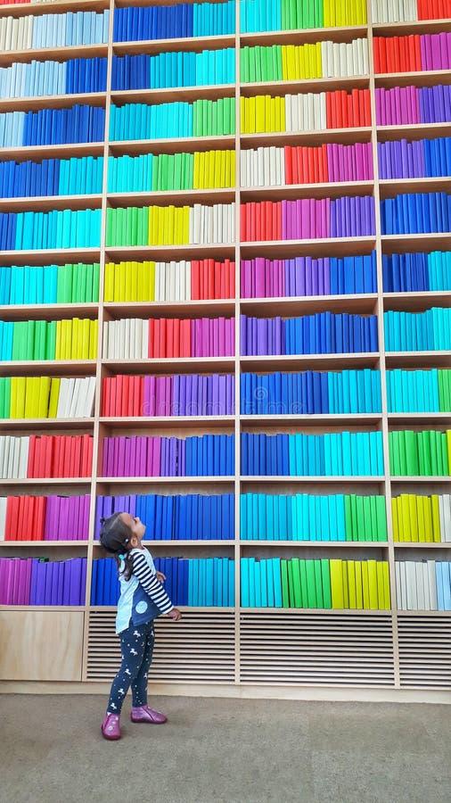 Um bebê novo na posição da biblioteca perto de uma estante infinita com fileira colorida dos livros foto de stock