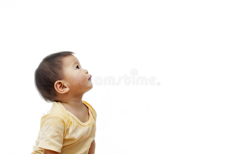 Um bebê olha acima com a roupa amarela, não olhando a câmera, isolada no branco imagem de stock