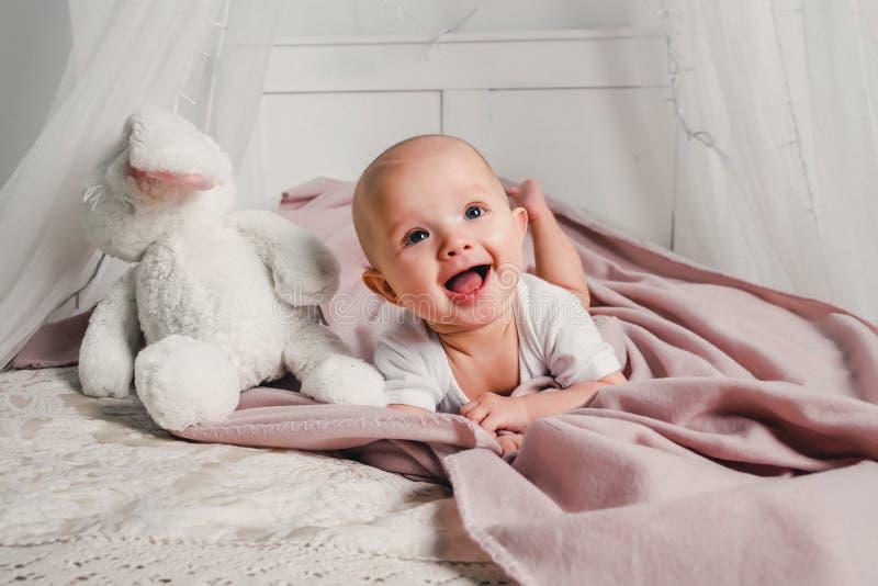 Um bebê pequeno coloca em uma cama com um coelho do brinquedo e sorri fotos de stock royalty free
