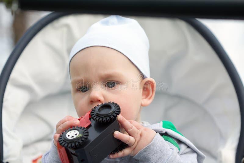 Um bebê pequeno engraçado na em um transporte de bebê imagens de stock royalty free