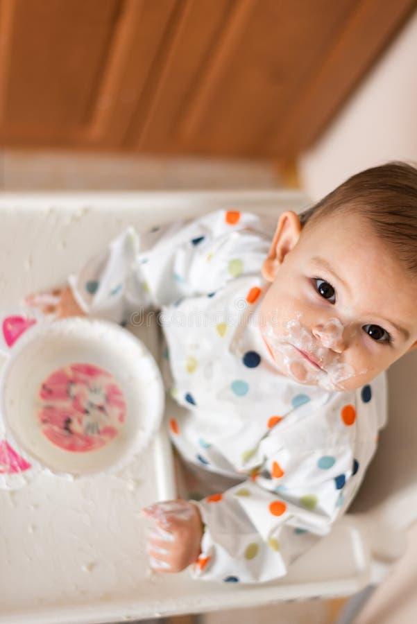 Um beb? pequeno que come seu jantar e que faz uma confus?o imagem de stock