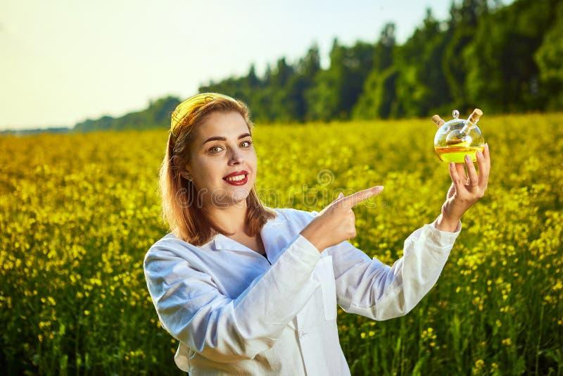 Um biólogo ou um agrônomo bonito novo examinam a qualidade do óleo de colza em um campo da violação Conceito do neg?cio agr?rio fotos de stock royalty free