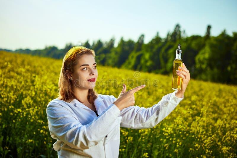 Um biólogo ou um agrônomo bonito novo examinam a qualidade do óleo de colza em um campo da violação Conceito do neg?cio agr?rio foto de stock royalty free