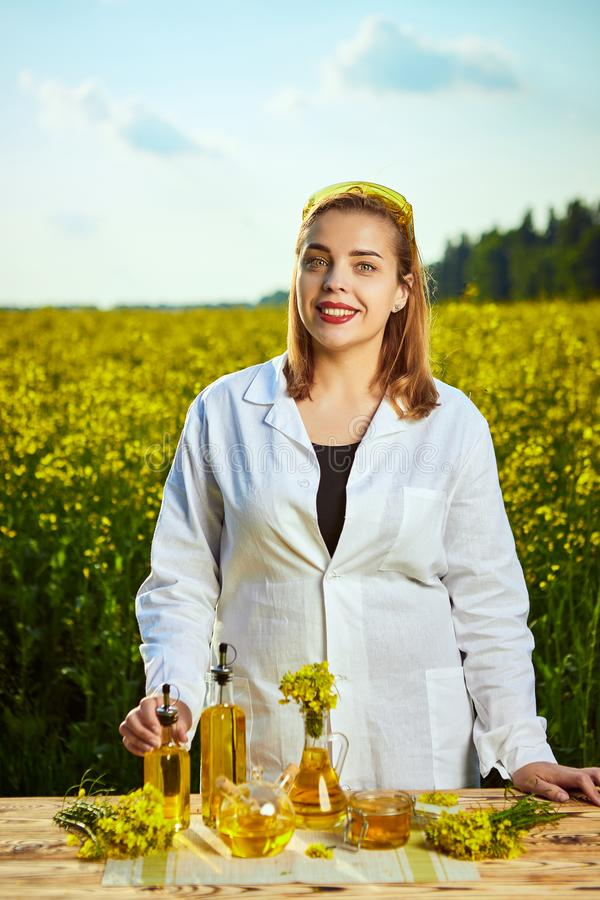 Um biólogo ou um agrônomo bonito novo examinam a qualidade do óleo de colza em um campo da violação Conceito do neg?cio agr?rio foto de stock