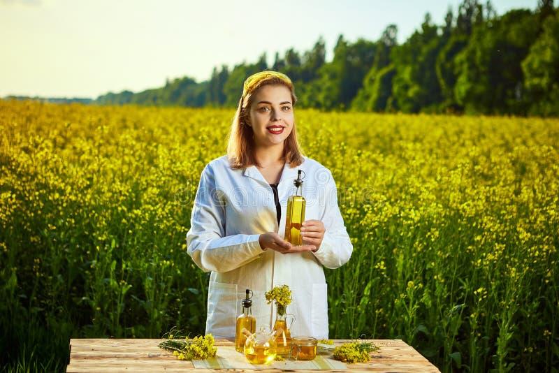 Um biólogo ou um agrônomo bonito novo examinam a qualidade do óleo de colza em um campo da violação Conceito do neg?cio agr?rio imagem de stock royalty free