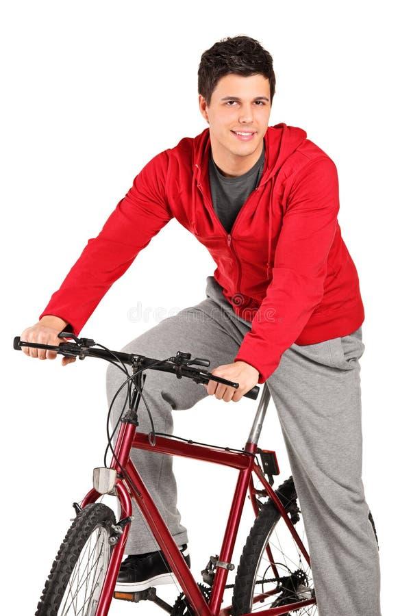 Um bicyclist de sorriso em um levantamento da bicicleta fotos de stock