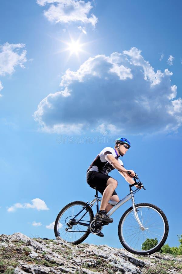Um bicyclist que monta um estilo em declive da bicicleta de montanha imagens de stock