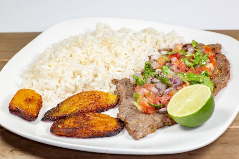 Um bife coberto em pico de Gallo cercado por banana-da-terra e pelo arroz branco em uma placa branca Alimento cubano foto de stock