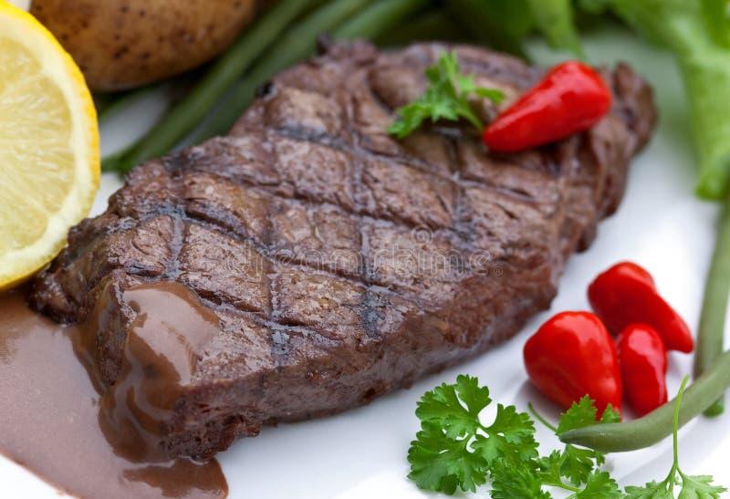 Um bife de tira do sirloin com vegetais e savory fotografia de stock