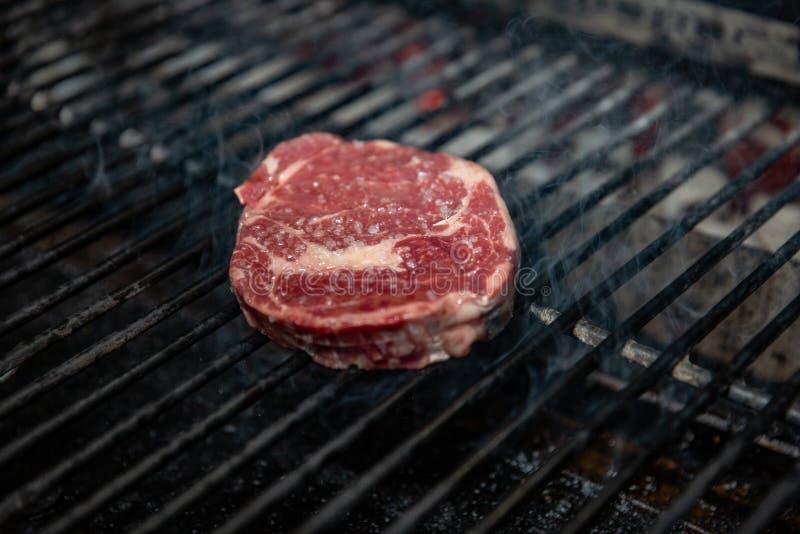 Um bife grosso perfeito do lombo da tira de New York de 1 polegada, temperado e churrasco sobre a chama no assado fotos de stock royalty free