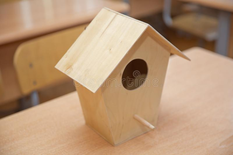 Um Birdhouse na neve Pouco casa do pássaro que pendura entre ramos O ninho do pássaro de madeira imagens de stock royalty free