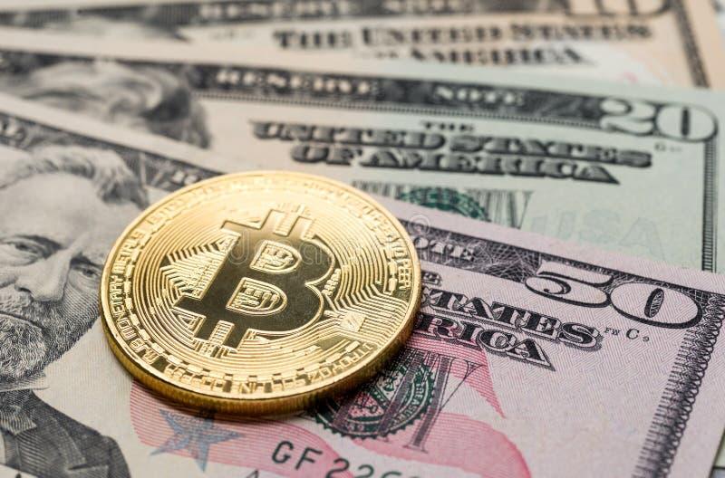 Um bitcoin com notas de dólar imagens de stock royalty free