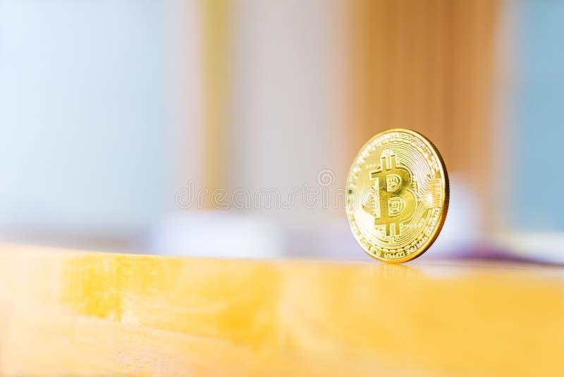 Um Bitcoin, moeda do cryptocurrency, estando na tabela de madeira, reflecti foto de stock royalty free