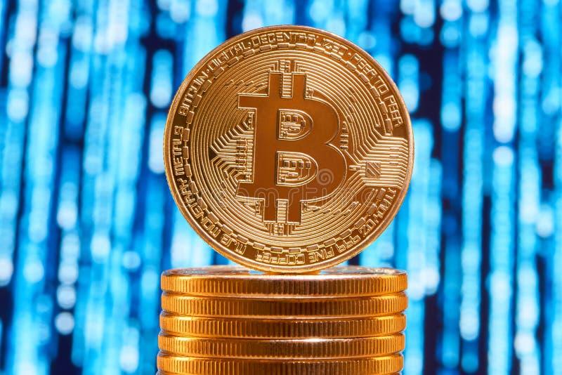 Um bitcoin na borda colocada na pilha de bitcoins dourados com circuito azul borrado no fundo fotos de stock