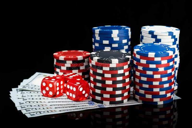Um bloco de cem notas de dólar cobertas com as microplaquetas e os ossos para jogar o pôquer em um fundo preto imagens de stock royalty free