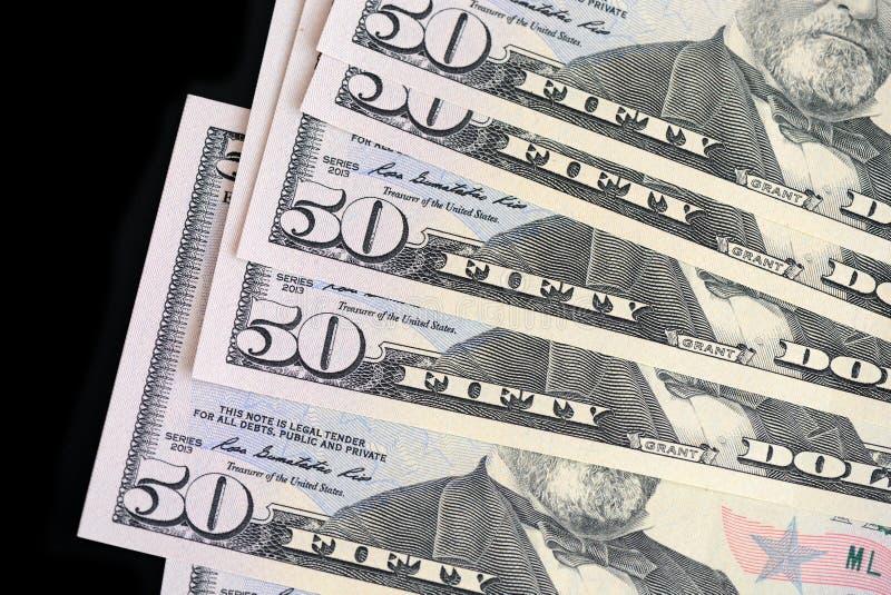 Um bloco de cinqüênta notas de dólar em um fundo escuro imagens de stock