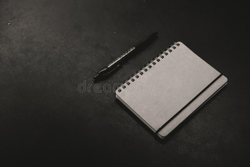 Um bloco de notas com uma pena em um fundo escuro foto de stock royalty free