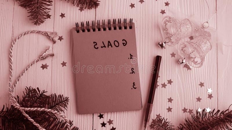 Um bloco de notas em uma tabela de madeira perto da árvore de Natal Caderno a fotografia de stock royalty free