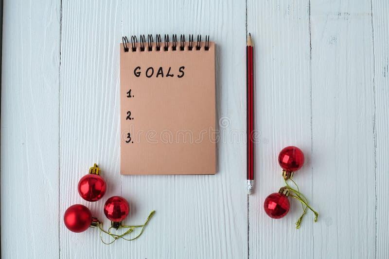 Um bloco de notas em uma tabela de madeira perto da árvore de Natal Caderno a foto de stock