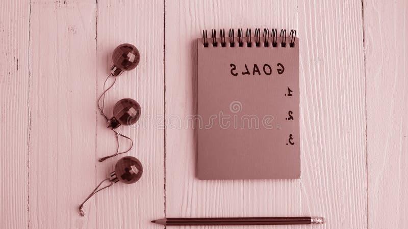 Um bloco de notas em uma tabela de madeira perto da árvore de Natal Caderno a imagens de stock