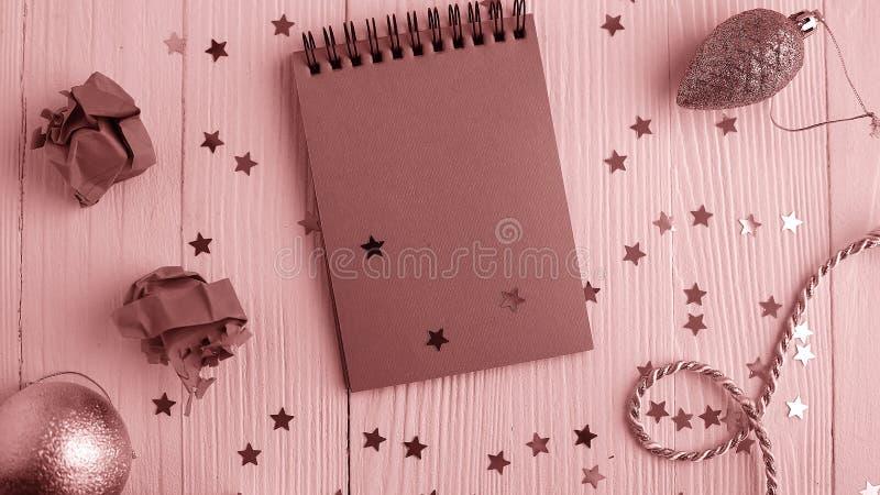 Um bloco de notas em uma tabela de madeira perto da árvore de Natal Caderno a fotos de stock