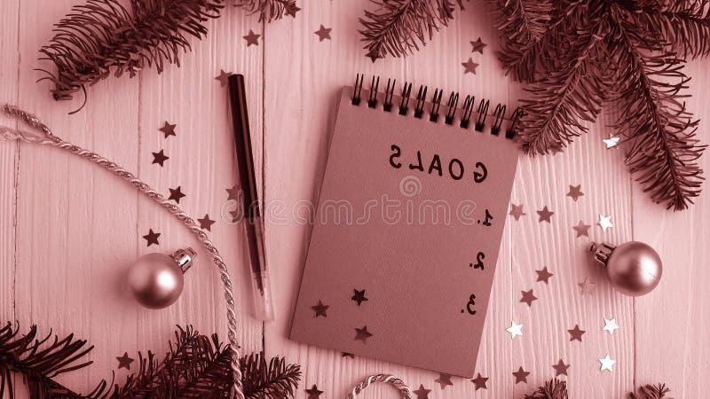 Um bloco de notas em uma tabela de madeira perto da árvore de Natal Caderno a fotografia de stock