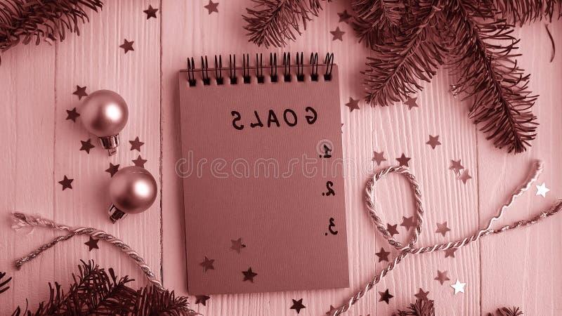 Um bloco de notas em uma tabela de madeira perto da árvore de Natal Caderno a foto de stock royalty free