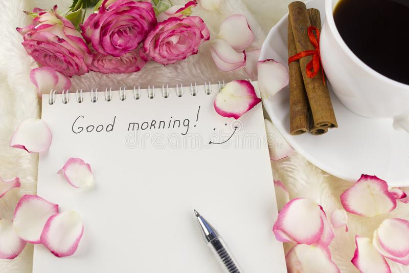 Um bloco de notas limpo com o bom dia da inscrição, pétalas cor-de-rosa, notas do café imagens de stock royalty free