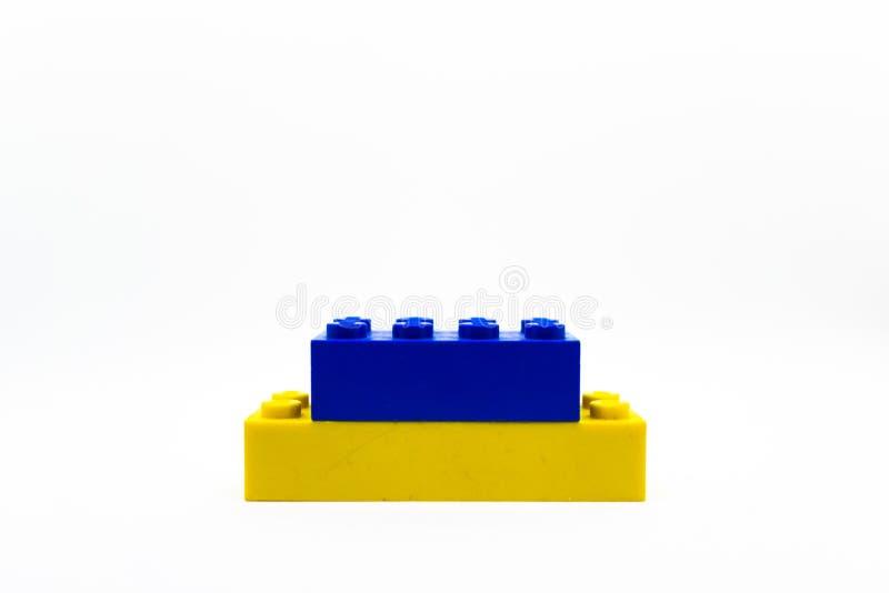 Um bloco pequeno azul e amarelo de Lego isolado no fundo branco imagem de stock