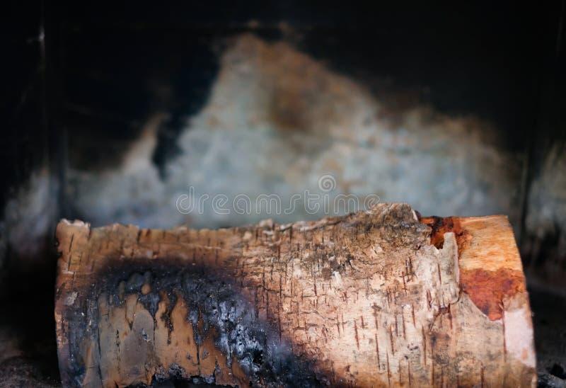 Um bocado queimou a lenha encontra-se na chaminé ou no fogão contra fotos de stock