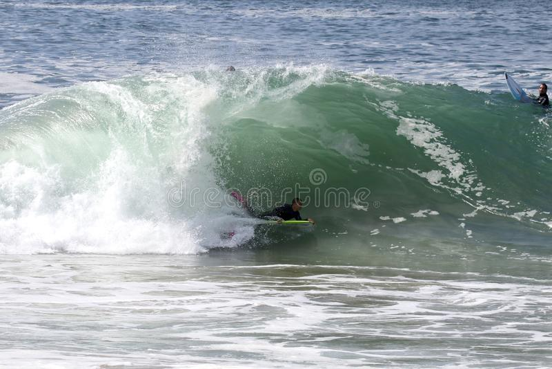 Um bodyboarder que trava uma onda na cunha na praia de Newport foto de stock