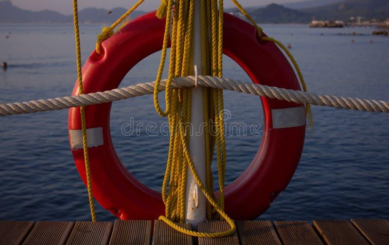 Um boia salva-vidas vermelho e umas cordas amarelas estão pendurando no cais fotos de stock