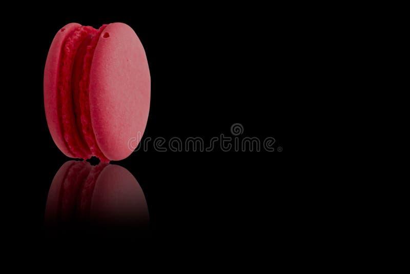 Um bolinho de amêndoa vermelho no fundo preto fotografia de stock