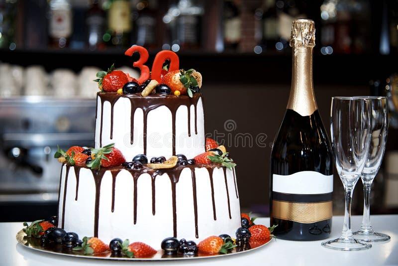 Um bolo branco a dois níveis com fruto fresco e chocolate está ao lado de uma garrafa do champanhe e do bokalam dois foto de stock royalty free