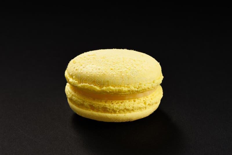 Um bolo da cor do limão do amarelo do macarrão Bolinho de amêndoa delicioso isolado no fundo preto Cookie doce francesa imagens de stock royalty free