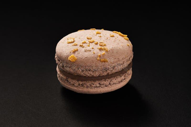 Um bolo da cor do marrom do macarrão Bolinho de amêndoa delicioso do chocolate isolado no fundo preto Cookie doce francesa imagens de stock royalty free