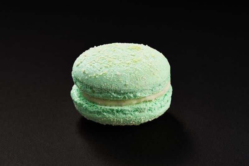 Um bolo da cor da hortelã do macarrão Bolinho de amêndoa delicioso isolado no fundo preto Cookie doce francesa fotos de stock
