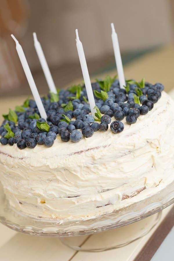 Um bolo de aniversário branco grande com os mirtilos orgânicos frescos e velas do hortelã e as brancas na parte superior fotos de stock royalty free