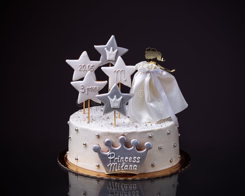 Um bolo de aniversário para uma menina com uma princesa da boneca Fundo preto imagem de stock royalty free