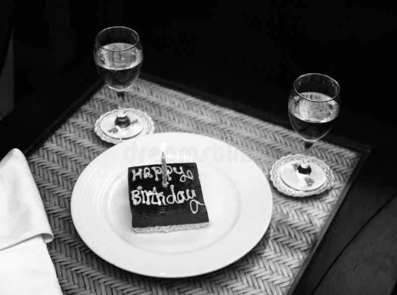 Um bolo de aniversário quadrado pequeno do chocolate com o happ da inscrição fotos de stock royalty free