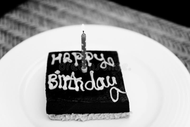 Um bolo de aniversário quadrado pequeno do chocolate com o happ da inscrição imagens de stock royalty free