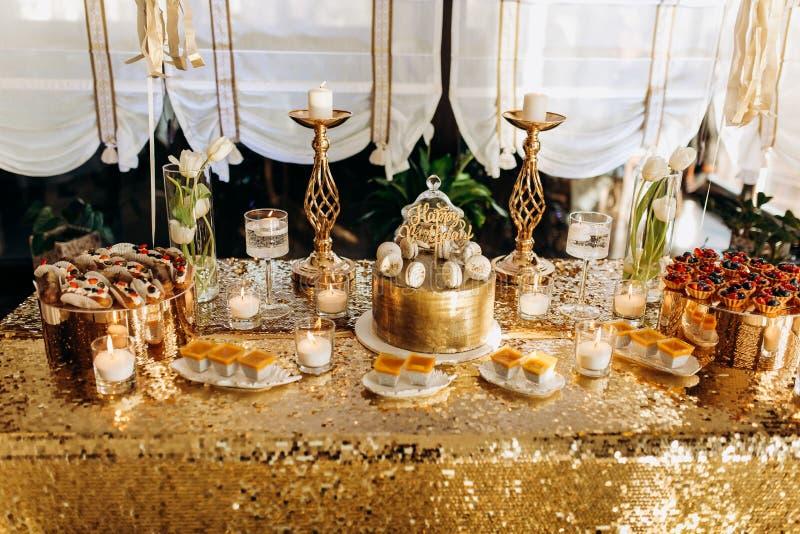 Um bolo de anivers?rio dourado ? decorado com macarr?o fotos de stock royalty free