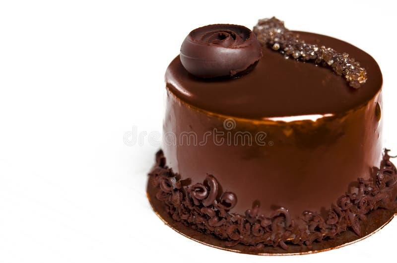 Um bolo de chocolate delicioso com partes do chocolate encontra-se em um suporte de madeira ao lado de um copo branco, que esteja imagens de stock royalty free
