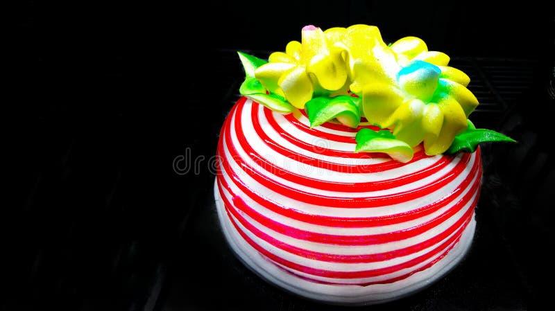 Um bolo delicioso bonito isolado no fundo preto fotografia de stock royalty free